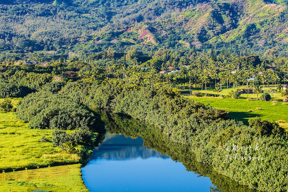 The Hanalei River, hau bush and mountains reflected in its calm surface, Kauai, Hawaii