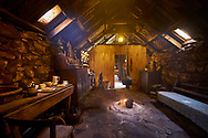 Original interior of the kitchen area with paet fire burning in The Blackhouse, 24 Arnol, Bragar, Isle of Lewis, Scotland. .<br /> <br /> Visit our SCOTLAND HISTORIC PLACXES PHOTO COLLECTIONS for more photos to download or buy as wall art prints https://funkystock.photoshelter.com/gallery-collection/Images-of-Scotland-Scotish-Historic-Places-Pictures-Photos/C0000eJg00xiv_iQ