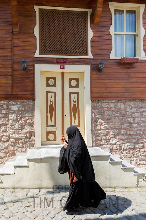 Muslim woman in traditional niqab veil clothing in the area of Kariye Muzesi, Edirnekapi in Istanbul, Republic of Turkey