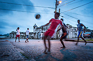 A man kicks a soccer ball in front of Fort San Jeronimo, Panama.