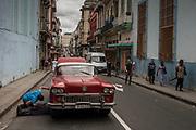 A mechanic tries to fix a broken down car in a busy street in Havana, Cuba.