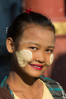 MANDALAY, MYANMAR - NOVEMBER 30, 2016 : one young smiling woman portrait face wearing Thanaka  traditional make up in Myanmar (Burma)