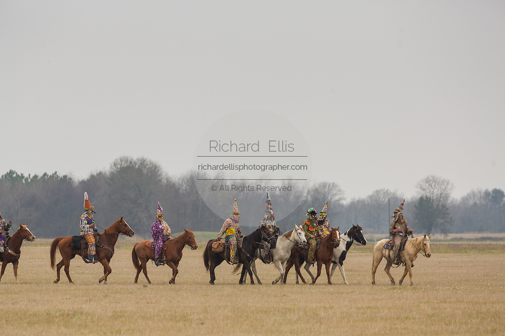 Costumed revelers on horseback during the traditional Cajun Courir de Mardi Gras chicken run February 15, 2015 in Church Point, Louisiana. The event involves 900-hundred costumed revelers competing to catch a live chickens as they move from house to house throughout the rural community.