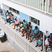 INDIVIDUAL(S) PHOTOGRAPHED: N/A. LOCATION: St. Damien Hospital, Nos Petits Frères et Sœurs, Tabarre 41 Commune, Haïti. CAPTION: People waiting for treatment sit on benches on a balcony at St. Damien Hospital.