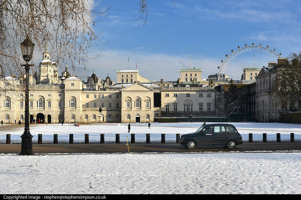 © Licensed to London News Pictures. 21/01/2013. Westminster, UK A famous London black cab travels along Horseguards with the London Eye seen in the distance. . Snow in the Royal Park, St James Park, in Central London today 21 January 2013. Photo credit : Stephen Simpson/LNP