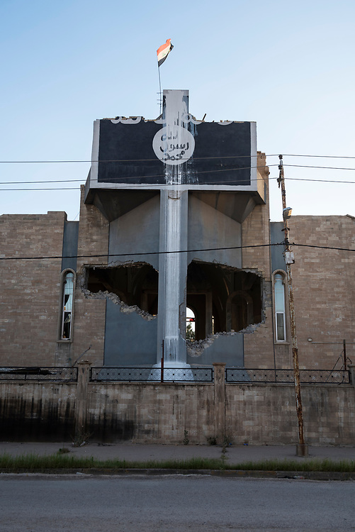 An Iraqi flag flies from the top of the heavily damaged Church of St. Ephraim, a Syriac Orthodox church, in Mosul, Iraq, in the months after this part of Mosul was taken from ISIS. The ISIS emblem was painted on the front of the building during the ISIS occupation of Mosul. (May 24, 2017)