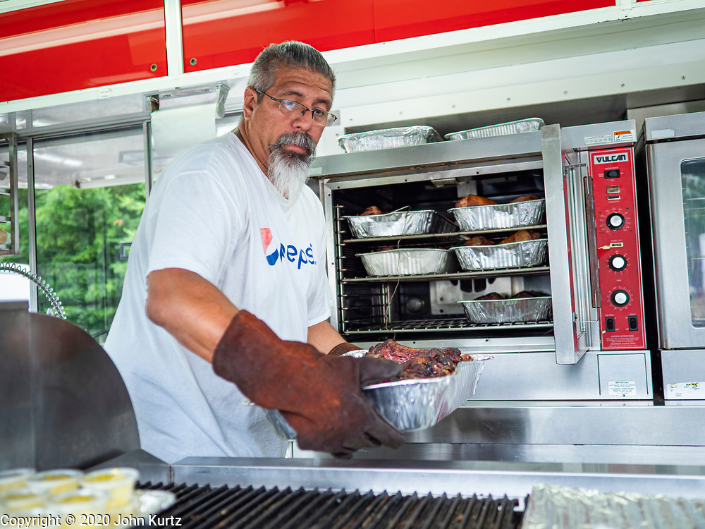 """26 JUNE 2020 - DES MOINES, IOWA: PAT GARCIA serves grilled turkey legs in the Turkey Time booth at Fair Food Friday in Des Moines. The 2020 Iowa State Fair, like many state fairs in the Midwest, has been cancelled this year because of the COVID-19 (Coronavirus) pandemic. The cancellation of the fair left many small vendors stranded with no income. Some of the fair food vendors in Iowa started """"Fair Food Fridays"""" on a property a few miles south of the State Fairgrounds. People drive up and don't leave their cars while vendors bring them the usual midway fare; corndogs, fried tenderloin sandwiches, turkey legs, deep fried Oreos, lemonaide and smoothies. Fair Food Friday has been very successful. The vendors serve 450-500 people per Friday and during the lunch rush people wait in line in their cars 30 - 45 minutes to place an order.      PHOTO BY JACK KURTZ"""