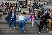 Large ladies and child in Trafalgar Square, London. We see across the busy tourist location in the capital to the crowds on steps and on the wall of the fountains - most prominently is the large backside of a woman leaning on stonework, her denim jeans tight across her posterior. A young girl sits alongside - perhaps sharing the same family genes.