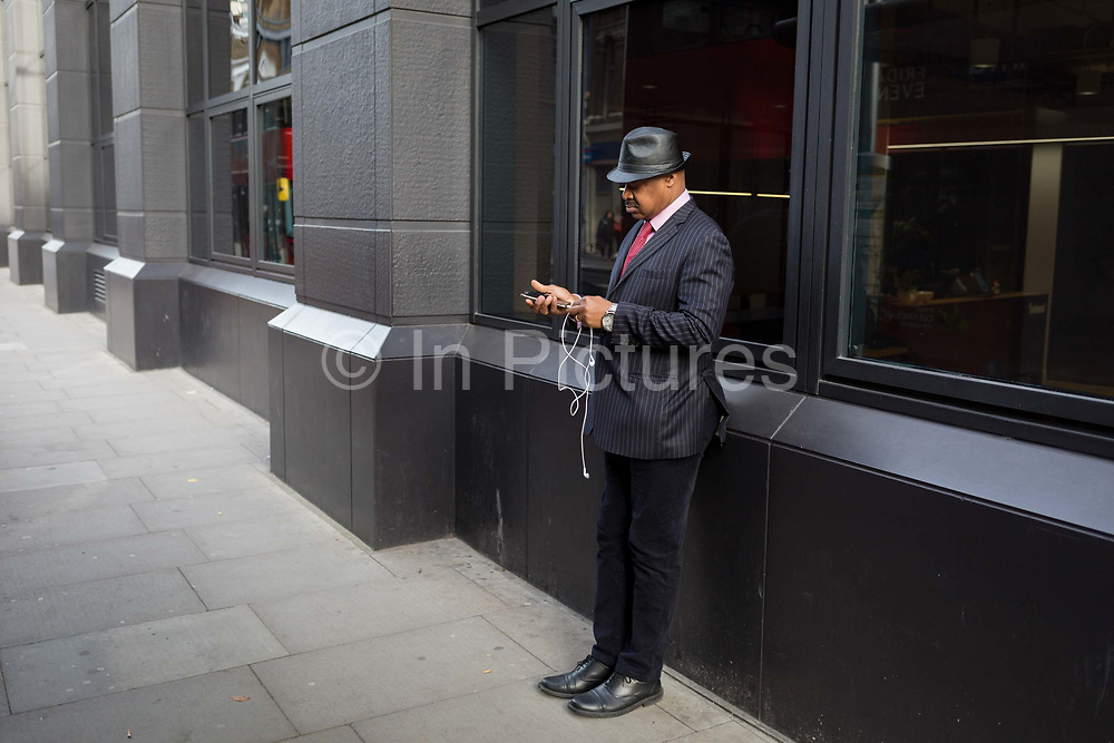 A man listens via headphones at a bus stop on Farringdon Road, on 20th November 2019, in the City of London, England.