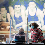 CHARLOTTE, NC - OCT 15: Poll workers who check voters in before they cast a ballot change shifts during a lull  inside the Spectrum Center on the first day of early voting in Charlotte, North Carolina on October 15, 2020.  Many large sporting venues in the city offered their buildings for early voting  to allow greating social distancing for voters and volunteers. Polling locations have also been retrofit with extra personal protective equipment to combat the spread of COVID-19 while early voting in the state of North Carolina runs from October 15th to October 31st. (Photo by Logan Cyrus for The Washington Post)