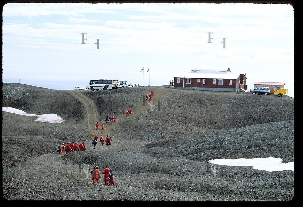 Tourists walk rocky moonscape to Joklasel restaurant, Iceland's highest (840m), after snowmobiling Vatnajokull; Iceland.