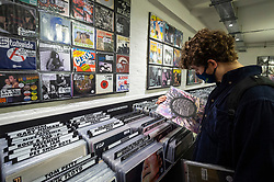 © Licensed to London News Pictures. 12/06/2021. LONDON, UK. A customer in Sister Ray Records in Soho on Record Store Day, where independent record shops worldwide celebrate music, including special vinyl releases made exclusively for the day. In the UK, vinyl sales have increased for the 13th consecutive year.  The BPI reported that nearly 5m records were sold in the 2020 in the UK as, with more time spent at home, music lovers had time to add to their collections.  Photo credit: Stephen Chung/LNP