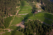 Vineyards and farm in the southern Eisack valley region near the South Tyrolean town of Klausen-Chiusa in northern Italy. We look down from the path leading to Säben Abbey high above the town. The slopes of vineyards of the central Eisack valley have a high mineral content of the soil, large fluctuations in temperature between hot, southern days and cool alpine mountain nights. According to the 2011 census, there are 505,000 inhabitants in south Tyrol.