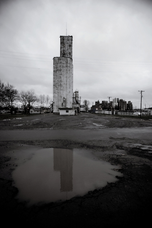 black and white of grain silo in small town Arkansas reflected in a water puddle