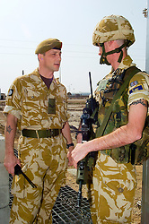 A British soldier, from the Muliti National Division (MND SE) speaks with a corporal at a  security gate, Allenby Lines on Basra Air Station during Operation Telic in March 2005