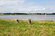 Summer landscape view of bench overlooking sailing boats on River Deben estuary, Sutton, Suffolk, England, UK