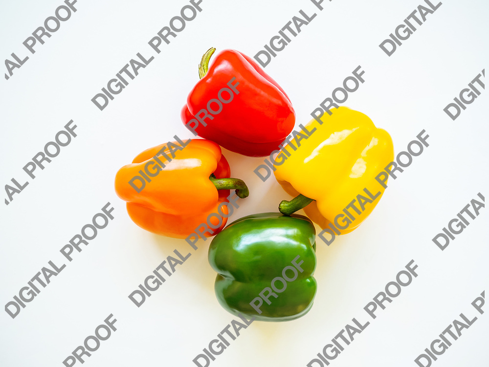 Group of red, green, yellow, and orange bell peppers isolated in white background in studio