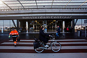 In Amsterdam passeren fietsers het Centraal Station over het zebrapad. Een werkman steekt over.<br /> <br /> In Amsterdam cyclists pass Amsterdam Central Station over a crossing.