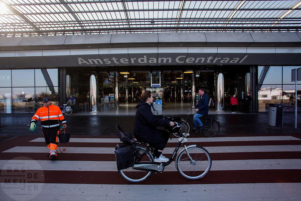 In Amsterdam passeren fietsers het Centraal Station over het zebrapad. Een werkman steekt over.<br /> <br /> In Amsterdam cyclists pass Amsterdam Central Station over a crossing.