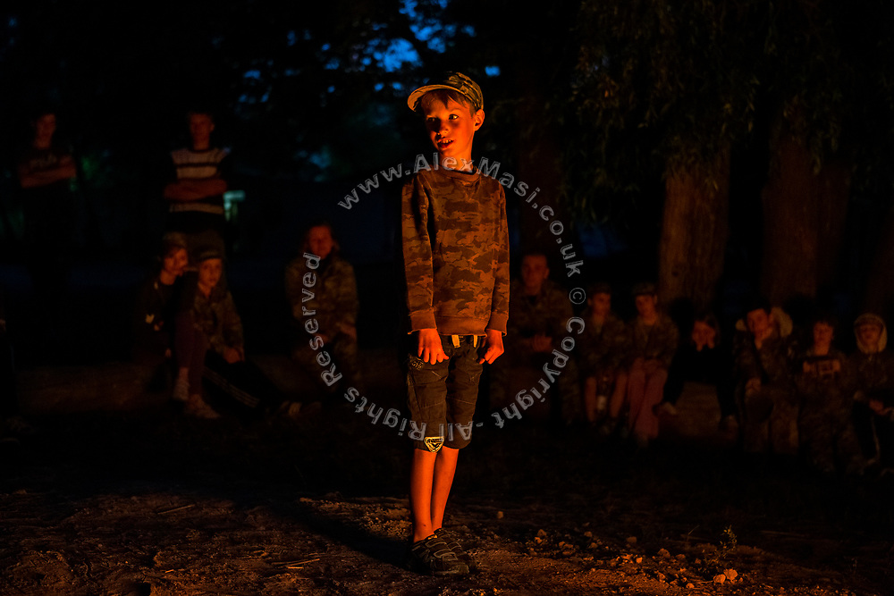 Around the evening fire, a boy is introducing himself to the other youngsters participating to the ultra-nationalistic Azovets children's camp, on the banks of the Dnieper river in Kiev, Ukraine's capital.