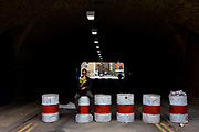 A man reads a book while sitting astride an old concrete-filled oil drums at the entrance to an East London railway tunnel. Wearing dark glasses and reading a book about successful business plans. The six solid drums serve as a heavy deterrent for any vehicles expecting to drive through the dark underpass. This is near Brick Lane, an area of now mainly the Bangladeshi and artists' community  but also of a new development of cross-London railways that have changed the area irreversibly. The tunnel is a turning off Sclater Street that formed part of Isambard Kingdom Brunel's subterranean Bishopgate Goodsyard in use between 1840 to 1964. Partly demolished in 2004, the rails now carry overland trains on the Crossrail project.