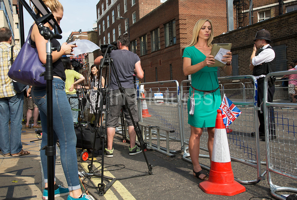 London, UK. Monday 22nd July 2013. Italian Sky News television anchor shooting a piece to camera. Media frenzy outside St Mary's Hospital in London on the day that Kate Middleton Duchess of Cambridge was taken into hospital after going into labour. Immediately the global media village began to buzz with activity and the Royalist public started to arrive in numbers.