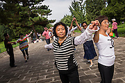 Chinese people dance at the Temple of Heaven Park during summer in Beijing, China