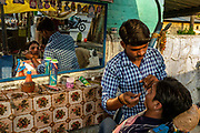 A barber threads a man's eyebrows at a roadside stall in New Delhi, India.