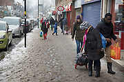 People struggle to go about their daily lives in freezing weather as snow turns to slush, dubbed The Beast from the East due to the sub zero cold temperature winds coming in from Siberia, descends on Kings Heath High Street on 3rd March 2018 in Birmingham, United Kingdom.