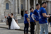 A Chinese wedding couple stand outside St. Paul's Cathedral alongside some Asian corporate achievers, on 25th March 2019, in London, England.