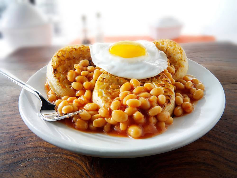Baked beans on crumpets with fried egg on top stock photos