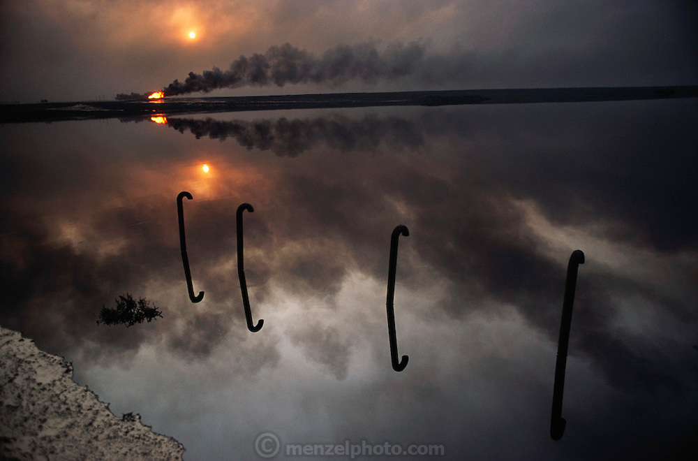 A lake of oil reflects a fire in the burning greater Al Burgan oil fields in Kuwait after the end of the Gulf War in May of 1991. More than 700 wells were set ablaze by retreating Iraqi troops creating the largest man-made environmental disaster in history.