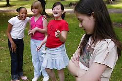 Three girls making fun of their friend,
