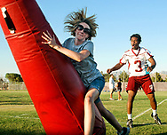 Robin Zielinski/Sun-News<br /> Kelsey Lenzmeier 26, of Las Cruces, run over a tackling dummy on Thursday during the Aggie Football 101 Women's Clinic as defensive back Donyae Coleman cheers her on at New Mexico State Univeristy.