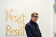 """New York, NY - 5 May 2017. The opening day of the Frieze Art Fair, showcasing modern and contemporary art presented by galleries from around the world, on Randall's Island in New York City. An example of political art, """"#ResistResist"""" by Kim Gordon, in the 303 Gallery."""