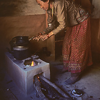 A Thakhali woman prepares tea on a stove built from mud in her kitchen in the Kali Gandaki Valley between Mounts Annapurna and Dhaulagiri in Nepal.