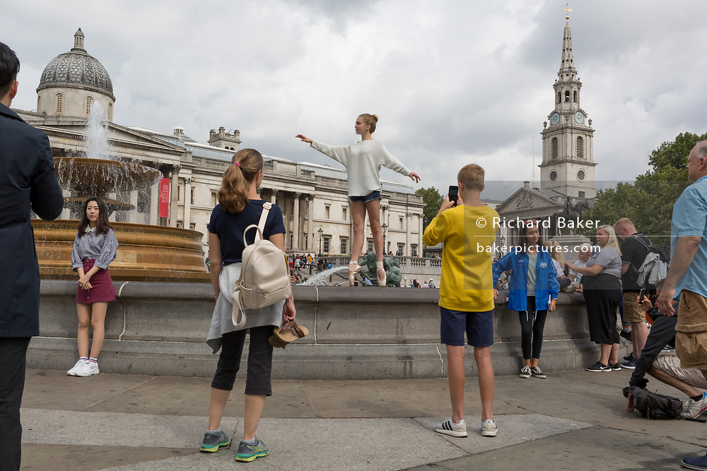 A young ballerina dancer adopts a position in front of the fountains of Trafalgar Square, on 13th August 2018, in London, England.