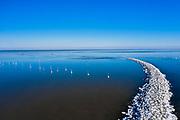Nederland, Flevoland, Trintelhaven; 22-02-2021; zicht op het IJsselmeer, richting Friese kust. Bevroren strekdam en boeien (palen) voor netten.  View of the IJsselmeer, towards the Frisian coast. Frozen breakwater and buoys (posts) for nets.<br /> <br /> drone-opname (luchtopname, toeslag op standaard tarieven);<br /> drone recording (aerial, additional fee required);<br /> copyright foto/photo Siebe Swart