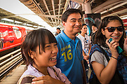 16 FEBRUARY 2013 - BANGKOK, THAILAND:   ABHISIT VEJJAJIVA, former Prime Minister of Thailand, (CENTER) poses for pictures with voters in the MoChit BTS station while campaigning for his party colleague Sukhumbhand Paribatra ahead of Bangkok's governor election. Bangkok residents go to the polls on March 3 to elect a new governor. Sukhumbhand Paribatra, the current governor, is running on the Democrat's ticket and is getting help from national politicians like Abhisit Vejjajiva, the former Thai Prime Minister. One of Sukhumbhand's campaign pledges is to improve Bangkok's mass transit and transportation system. Abhisist road the BTS Skytrain to campaign for Sukhumbhand.    PHOTO BY JACK KURTZ
