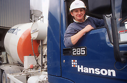 Female truck driver sitting in cab leaning out of window smiling,
