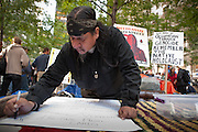 A native American man letters a sign asking for donations of computers and pre-paid phone cards.