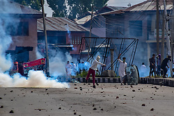 June 16, 2018 - Srinagar, Jammu & Kashmir, India - A kashmiri Protestor returns an exploded tear smoke shell towards paramilitary force during clashes after Eid ul-Fitr prayers in Srinagar on Saturday..Government Forces in Indian Administered Kashmir used tear gas and pellet guns to disperse hundreds of stone-throwing protesters who took to the streets after Eid al-Fitr prayers protesting against Indian rule on Saturday. (Credit Image: © Abbas Idrees/SOPA Images via ZUMA Wire)