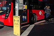 As the number of new Coronavirus cases in the UK climbs to 201,101, with UK deaths now standing at 30,076 - the highest recorded in Europe, a passenger enters the middle doors of a bus next to a Transport For London TFL sign asking the public to maintain safe social distances while travelling on the capitals public transport during the continuing Covid lockdown, on 6th May 2020, in south London, England. Front doors on London buses are now disabled to avoid exposure of drivers to the virus, plus no fares are being taken on journeys to further avoid card reader contact.