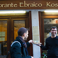 VENICE, ITALY - NOVEMBER 15: Member of staff Avishay offers appetizers in front of a koskher restaurant at the Venice Ghetto on November 15, 2011 in Venice, Italy. Established in 1516 the Ghetto of Venice was the area were Jews were compelled to live during the Venetian Republic. The English term 'ghetto' is derived from the Venetian term for 'slag' and refers to the refuse left the foundry that was located on the same island. In present times the ghetto is a multi-ethnical area area seen as the cultural heart of the city, but with five synagogues remains the centre of the of Jewish community.