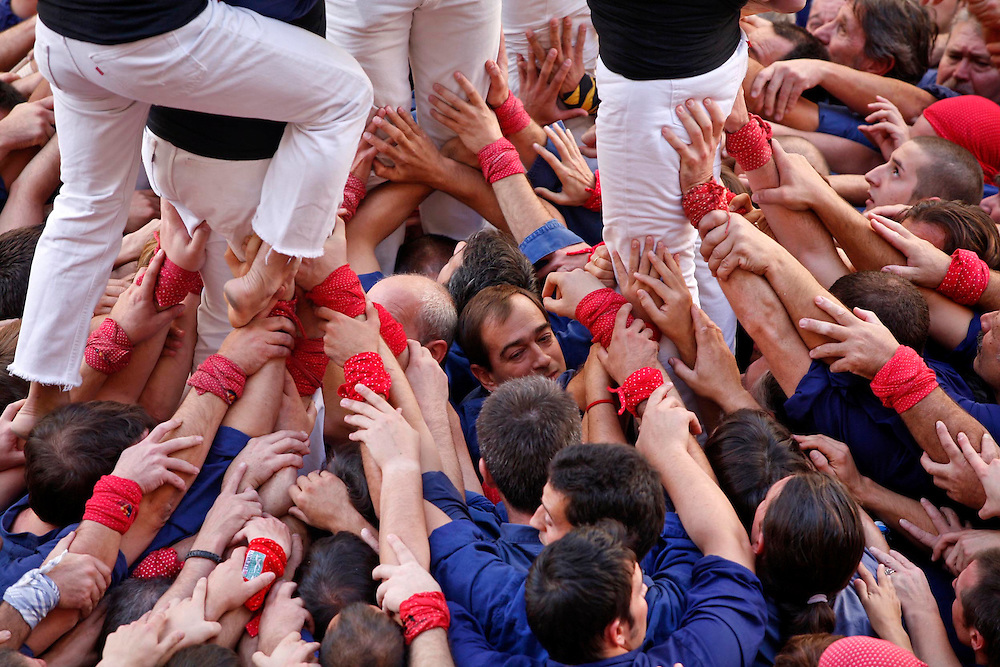 """The """"Castellers"""" (human towers)  are part of a Catalan popular festivity that consists of erecting human towers of several meters of height. """"Grallers"""" plays the instrument """"gralla""""  to give support to the people who are constructing the tower."""