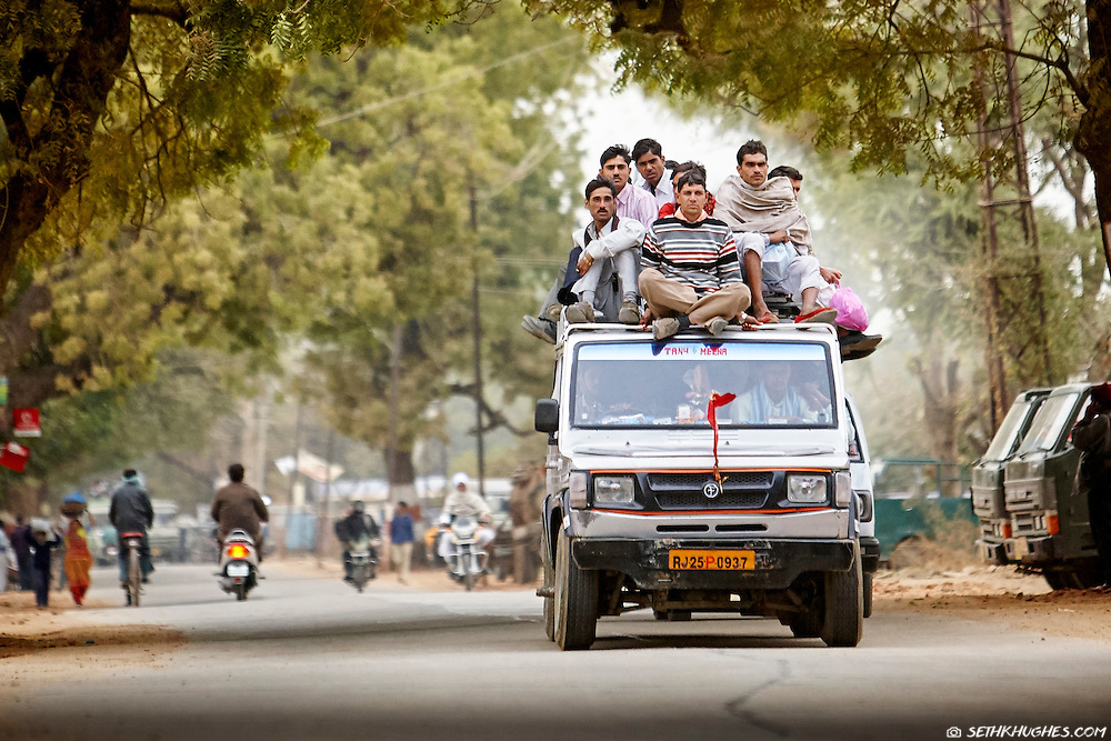 A group of Indian men commute via ride share on the roof of a Jeep in Ranthambore, Rajasthan.