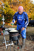68 year old Glen Sinclair cooking at camp stove after dirt bike race.  Glen and his family camp and ride together and camp on weekends at races.
