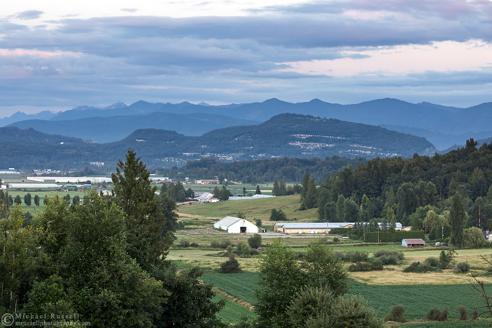 View of Abbotsford farmland and buildings with Sumas Mountain in the background.  Photographed in Abbotsford, British Columbia, Canada.