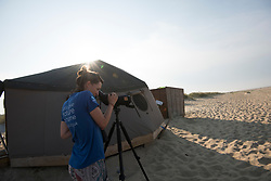 Project Officer Emma Witcutt observing colony from a distance using a scope, Little tern Sternula albifrons monitoring site, part of an EU Life Project to protect this species, Winterton-on-Sea, Norfolk, July