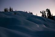 A lone snowshoer stands on ridge below Snow King Mountain, Glacier Peak Wilderness, Washington.